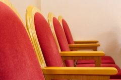 Row of red chairs in an empty concert hall close-up stock images