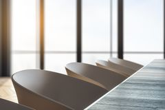 Row of office armchairs. And wooden desktop in modern meeting room interior. Blurry window background. Side view. 3D Rendering royalty free illustration