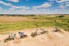 The row of oil derricks. Aerial view of the row of oil derricks in summer Royalty Free Stock Photos