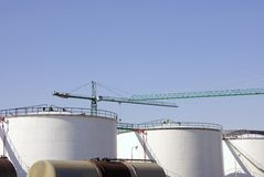 Row of oil storage tanks. Row of modern oil storage tanks with industrial cranes in background Royalty Free Stock Image