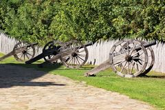 Row of old ancient vintage cannons on the green lawn against grey wooden palisade of the protective fence stakewall Stock Photography