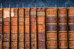 Row of old antique books in a library. Row of antique hard and softcover books books on shelf in a library stock image