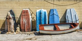 Row of old boats. A row of old boats stood on end in a boatyard in valletta, malta Stock Images