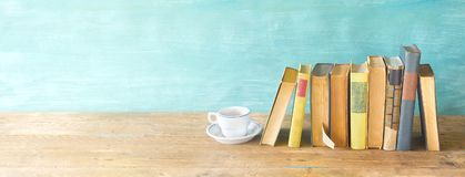 Row of old books and a cup of coffee on a rustic book shelf. Row of old books and a cup of coffe on a rustic book shelf panorma,reading, literature,education Stock Photos