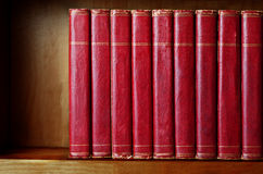 Row of Old Books on Shelf. A row of old, battered, matching encyclopaedias (circa 1950s) lined up on a shelf, with titles removed to leave blank spines.  Red Royalty Free Stock Photography