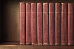 Row of Old Books on Shelf with Vintage Effect. A row of old, battered, matching encyclopaedias (circa 1950s) lined up on a shelf, with titles removed to leave Royalty Free Stock Photo