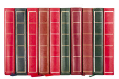 Row of Old Books Showing Spines. Row of old and worn books with the spines facing forward on an isolated white background with a clipping path Stock Photos