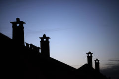 Row of old brick chimneys with moody evening sky. Row of old brick chimneys with moody bluish evening sky in the background Royalty Free Stock Image
