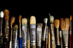 Row of old brushes. Old used art brushes lined in a row against black background stock photography