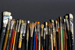 Row of old brushes. Old used art brushes lined in a row against black background royalty free stock photos