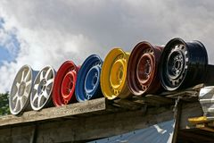 Row of old colored discs against the sky and clouds. A row of old colored car disks against the sky and clouds Stock Photography