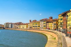 Row of old colorful buildings houses on embankment promenade of Arno river in historical centre of Pisa. Town with blue sky white clouds copy space background stock images