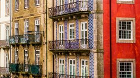Row of old, colorful buildings with ornate balconies and tiles line a street in Porto, Portugal stock images
