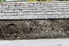 Row of old farm wheels leaning against a rustic old stone building. A row of old farm wheels leaning against a rustic old stone building Royalty Free Stock Image