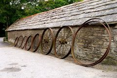Row of old farm wheels leaning against a rustic old stone building Stock Photos