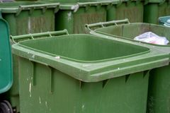 Row of old green trash bin in the community. Have a waste in the old green trash. Waste separation help reduce the amount of waste and recycle some types of Stock Photos