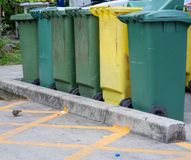 Row of old green and yellow trash bin in the community. Have a waste in the old green trash. Waste separation help reduce the amount of waste and recycle some Royalty Free Stock Photo