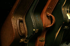 A Row of Old Guitar Cases. Close-up of a row of stacked, old and worn guitar cases Stock Images