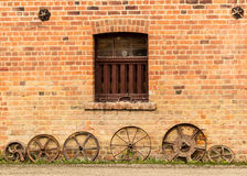 Row of old rusty cart wheels against barn. Old farming cartwheels leaning against aged brick of barn or farm building Stock Photography