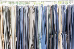 Row of old various woolen trousers. Close up row of various woolen trousers on hangers in tailoring atelier Royalty Free Stock Photos
