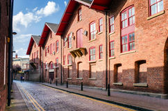 Row of Old Warehouses converted in Flats. Renovated Warehouses converted in Flats along a Narrow Cobbled Street. Leeds, England Stock Images