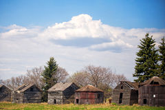 Row of old wooden sheds. A row of old weathered square wooden sheds and crumbling antique grain storage bins under cloudy sky in rural countryside landscape Stock Images