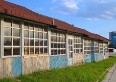 A row of one-storey wooden buildings under a common roof stock photo