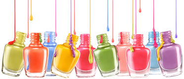 Row of open bottles of nail polish and a jets of dripping lacquer on white background. Stock Photos