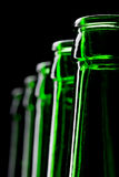 Row of open green beer bottles Stock Photo