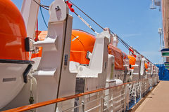 Row of Orange Lifeboats by Deck of Cruise Ship Stock Images
