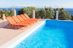 Row of orange loungers near blue swimming pool Stock Photos