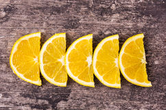 Row orange slices on wood background Stock Images