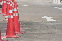 Row of orange traffic cones setting on roadway beside parking lot. Selective focus Stock Image