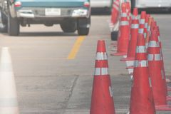 Row of orange traffic cones setting on roadway beside parking lot. Selective focus Royalty Free Stock Photo