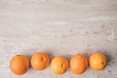 Row of oranges on marble surface. Top view of row of oranges on marble surface Royalty Free Stock Photography