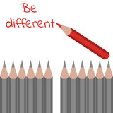 Row of ordinary grey pencils and one red with text - be differen Royalty Free Stock Photography