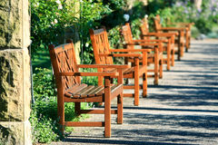 Row of outdoor garden seats. Row of outdoor timber garden seats in a park Stock Photo