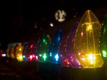Row of outdoor large Christmas lights. Row of outdoor oversized Christmas lights - dark - night image - blurred white lights in background Royalty Free Stock Images