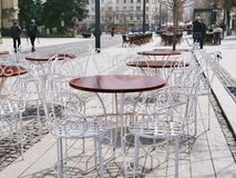 Row of outdoor teraces. Cluj-Napoca, Romania - March 30, 2018: Row of outdoor teraces on the Union square promenade. Beautiful white wrought iron chairs and Stock Images
