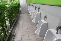 Row of outdoor urinal men public toilet white urinals in men bathroom Royalty Free Stock Images