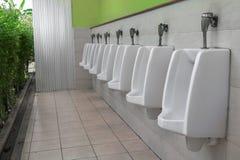 Row of outdoor urinal men public toilet white urinals in men bathroom Royalty Free Stock Photo