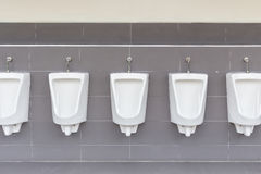 Row of outdoor urinals on grey wall in men public toilet Royalty Free Stock Images