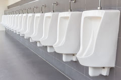 Row of outdoor urinals on grey wall in men public toilet. New row of outdoor urinals on grey wall in men public toilet Royalty Free Stock Photo