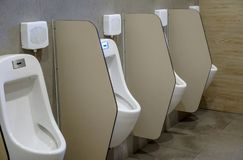 Row of outdoor urinals men in public toilet. Closeup white urina. Ls in men`s bathroom. Design of white ceramic urinals for men Stock Photography
