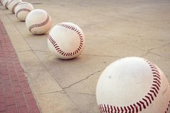 Oversized decorative baseballs form a path along a sidewalk stock photography