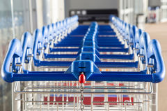 Row of paid luggage carts with a coin space and chain Royalty Free Stock Photos