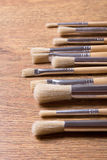 Row of paint brushes on wooden table background Royalty Free Stock Photos