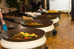 Row of pans with cooked food resting on a table Royalty Free Stock Photo