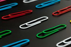 Row of paper clip on black background. Different concept Royalty Free Stock Photos