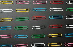 Row of paper clip on black background. Different concept Stock Photos